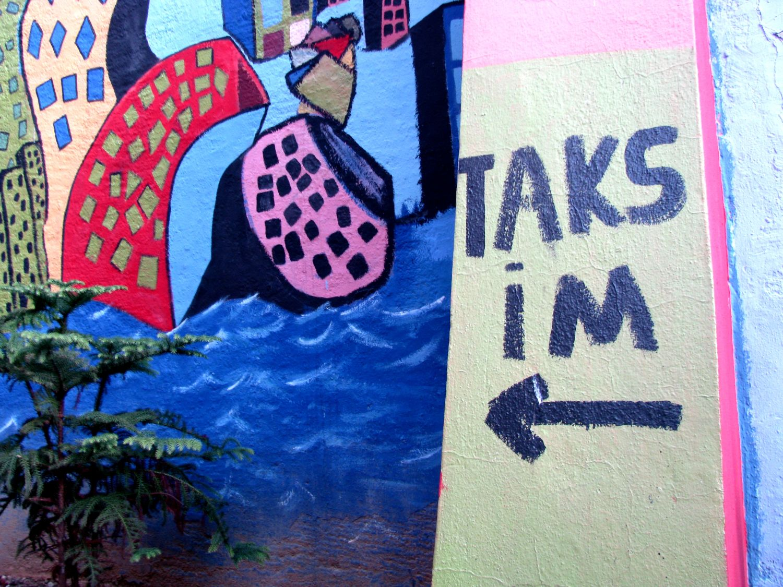 Kolorowy napis na murze kierujący do Taksim pieczone kasztany